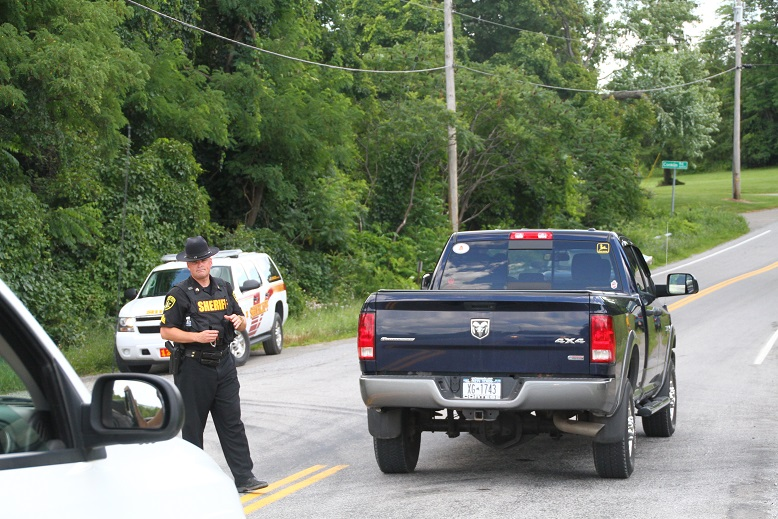 A Livingston County Sheriff's Deputy checks vehicles passing through the search area. (Photo/Conrad Baker)