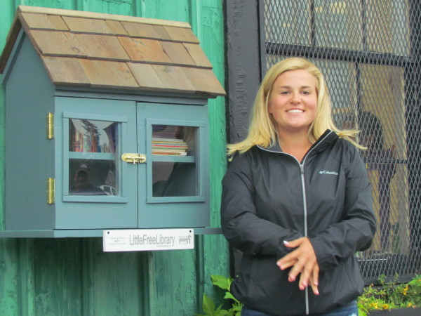 Megan Mikolajczyk with her Free Little Library in Highland Park (Photo Ariel Piazza)