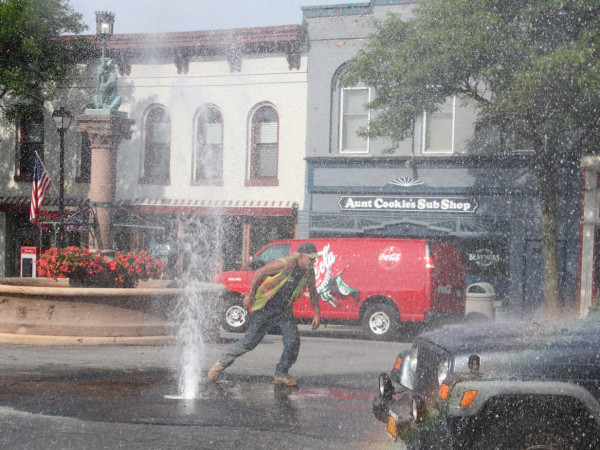 A construction worker handles a water issue near the bear fountain on Thursday. (Photo/Josh Williams)