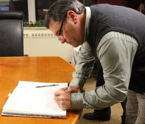 Griffo signs his name as a member of the Geneseo Town Council. (Photo/Conrad Baker)