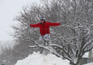 A young man jumps from Main Street Geneseo's snow mountain for a photo by his friends below.(Photo/Conrad Baker)
