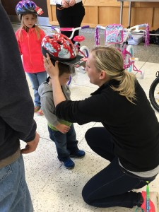 CCE Traffic Safety Educator Katelyn Sanders providing a helmet to a young winner. (Photo/CCE Livingston County)