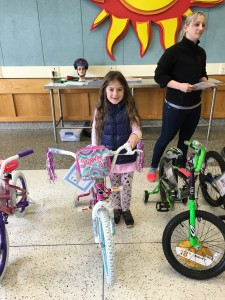 One of the coloring contest winners receiving their new bike. (Photo/CCE Livingston County)