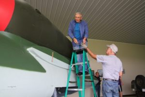 Lucas, top, removes hooks used to lower the model engine on the fuselage. (Photo/Conrad Baker)