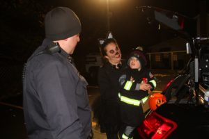 Officer DiPasquale shares some candy with a a young firefighter. (Photo/Conrad Baker)