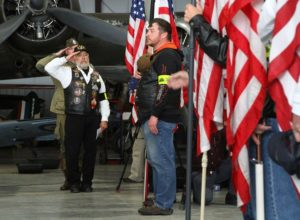 Don Higgins (far left), son of honoree Wallace Higgins, salutes for the National Anthem.(Photo/Conrad Baker)
