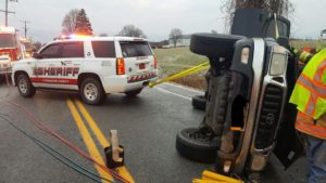 Deputy Martin Herkimer stabilizes the rolled vehicle with a tow strap until a tow truck arrives. (Photo/Livingston County Sheriff's Office)